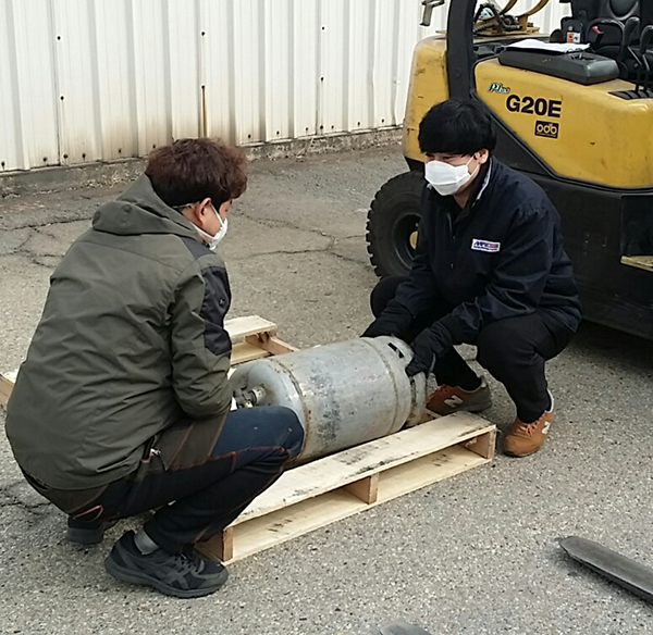 At the Korea Distribution Center, Storage Clerk Song-Hak Chon and MHE operator Yong-Po Sim use the team lift when replacing the forklift's gas tank.