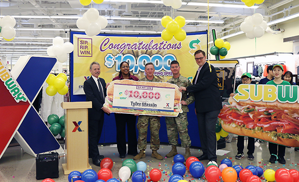 PFC Tyler Massie, center, stands with Pacific Region Vice President Rick Fair, Main Store Manager Debra Melton, BG Patrick Donohoe and General Manager Scott Bonner.