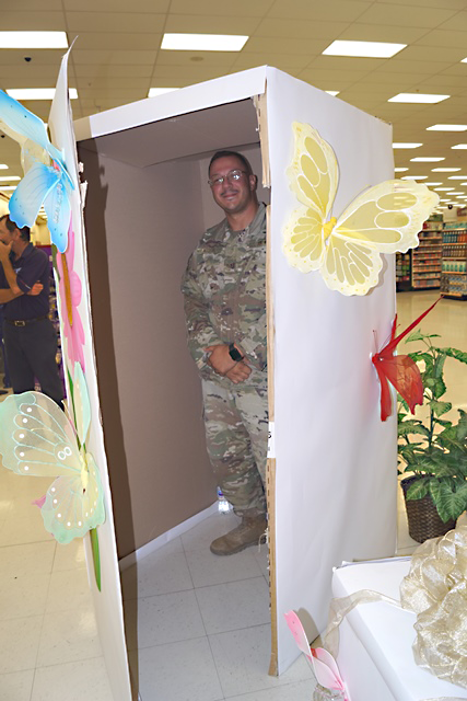 SSgt. Hector Acosta stands in the box that his daughter would soon open to find that her daddy had returned from deployment earlier than expected.