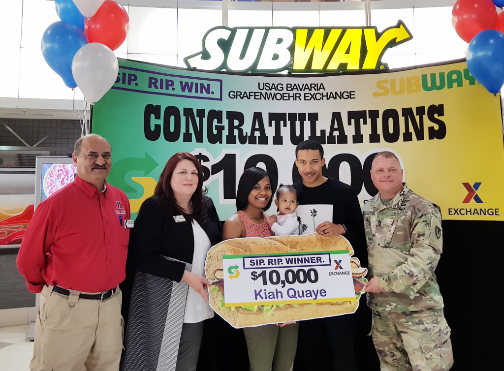 Exchange managers Aftab Khan and Carrie Cammel, along with USAG Bavaria CSM Micheal Sutterfield USAG Bavaria Command Sergeant Major present the $10,000 gift card to Kiah Quay and husband SPC Damion Quaye.