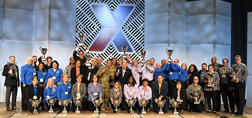 Main store managers and store managers hold up their trophies during their annual conference.