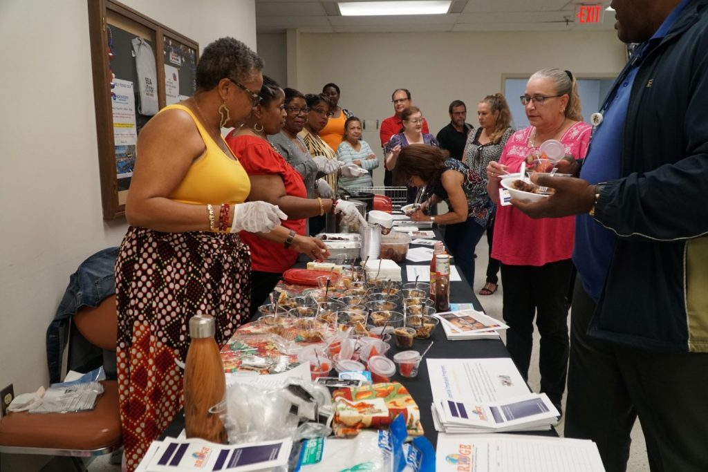 Members of BRIDGE serve cultural food samples to associates at Exchange HQ.
