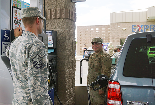 A members of the First Sergeants Council, left, pays for free gas. He even cleaned the vehicle's windshield.