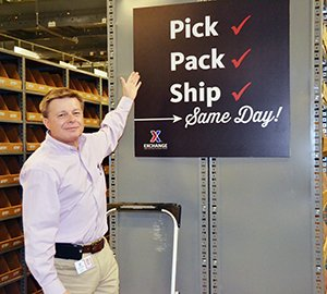 """Dave Nelson gestures at """"Pick, Pack, Ship - Same Day!"""" sign"""