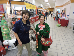 Misawa Main Store associates (left) Supervisory Sales Clerk Noriko Nomura and (right) Sales Clerk Satomi Mantoku bring holiday cheer to customers during a special event.