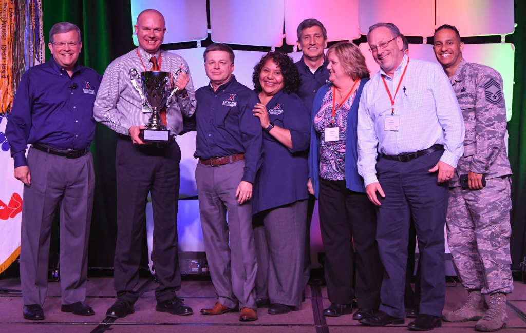 The UK Consolidated Exchange was awarded the Director/CEO Cup in the Large category at the annual Main Store Managers/General Managers Conference. Pictured (left to right): Exchange Director/CEO Tom Shull; UK Consolidated General Manager Edward Hicks; Chief Operating Officer Dave Nelson; President Ana Middleton; Chief Administrative Officer Phil Stevens; RAF Lakenheath Exchange Main Store Manager Sabine Brink; RAF Mildenhall Exchange Main Store Manager John Monaghan; and Chief Master Sgt. Luis Reyes.