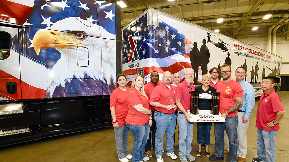 Members of Corporate Communication and the Logistics Directorate hold the big prize in front of the Exchange truck.