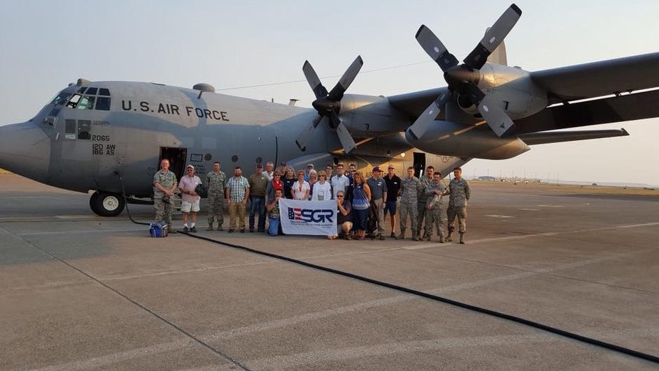 "Wanda Cummins and 24 other ""bosses"" pose in front of the C-130 plane that took them on an excursion over Central Montana."