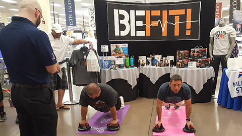 """NELLIS AFB, Nev - Associate Paul Ackerly officiates the perfect pushup contest during a """"Healthy Lifestyle"""" event that featured the Exchange's Be Fit products."""