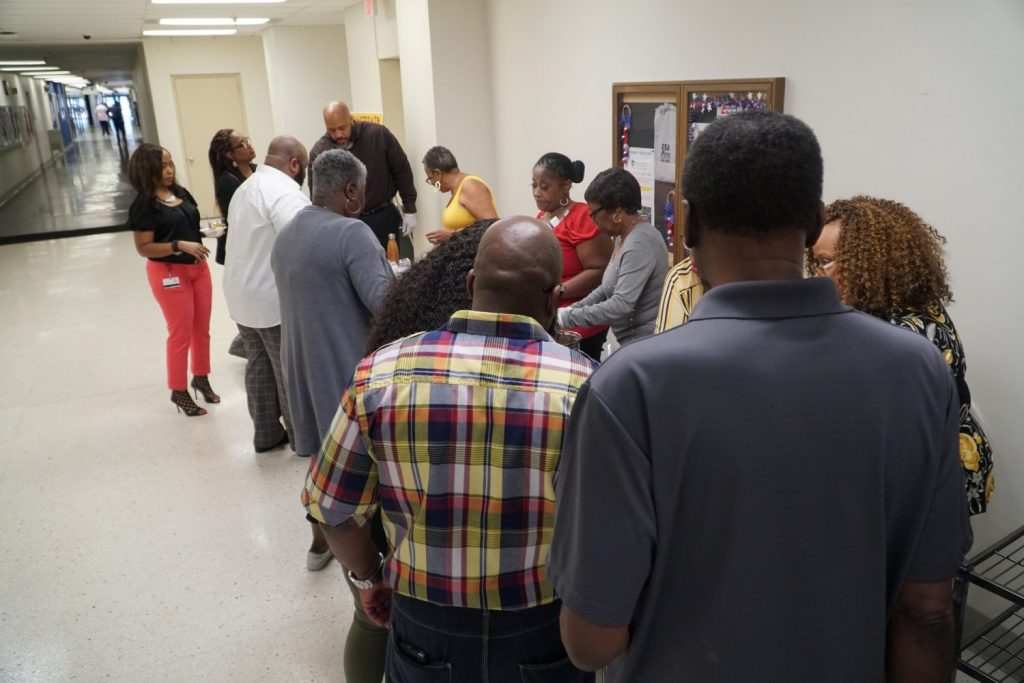 associates lined up for food samples