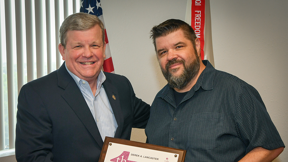 Director/CEO Tom Shull presents awards to Graphic Artist  Derek Lancaster. was presented the new coin from Exchange Director/CEO Tom Shull on July 10.