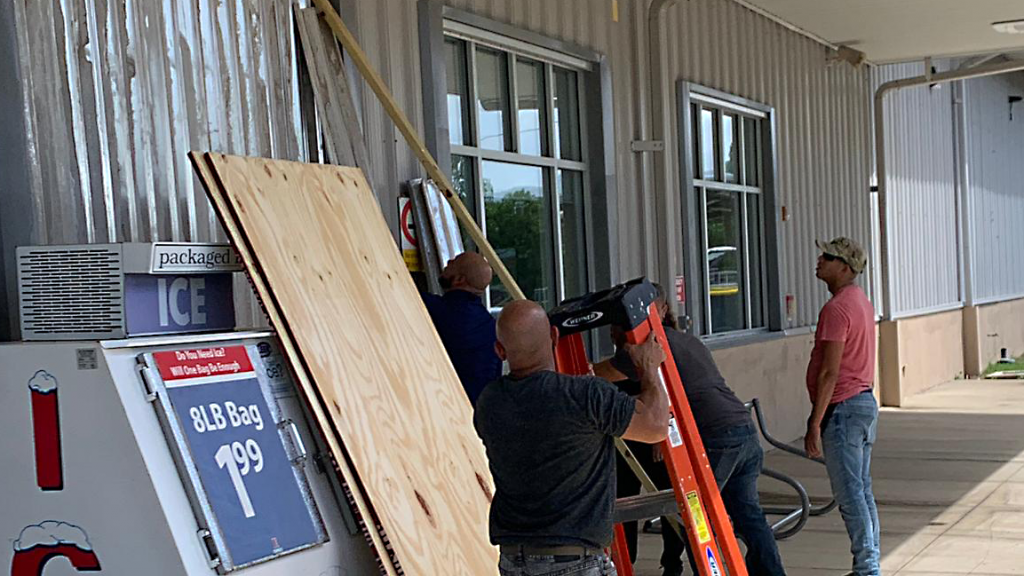 Workmen attach metal shutters to windows of the Camp Santiago Exchange in Puerto Rico to protect the building from storm damage.
