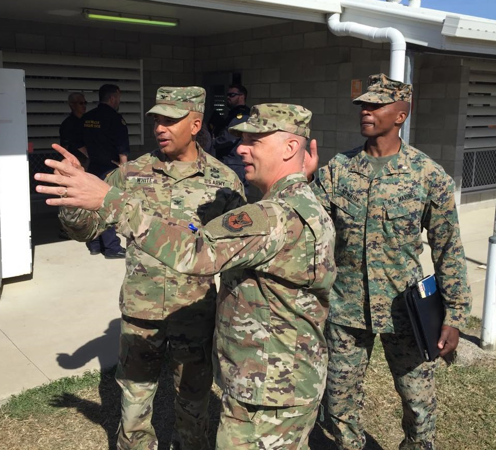 Exchange Pacific Region Commander Col Scott Maskery, center, talks with COL Ted White, member of the Exercise TALISMAN SABRE 2019 command team, and CWO4 Montreal Newkirk, MCCS Officer with Marine Corps Community Services, about capabilities and operations of a mobile field exchange to support Exercise Talisman Saber at Camp Rocky.