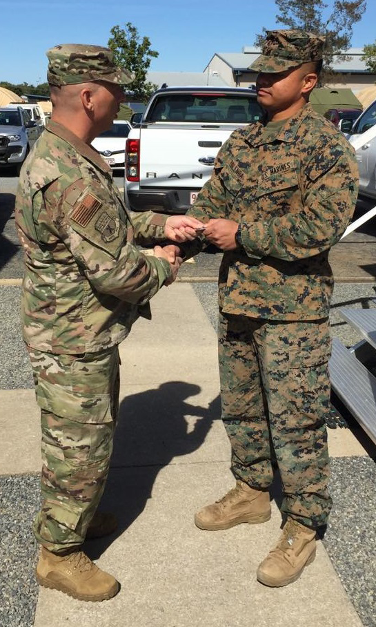 Exchange Pacific Region Commander Col Scott Maskery presents his Commander's Coin to SGT Jerry Tolenoa for his work operating a mobile field exchange to support Exercise Talisman Sabre at Camp Rocky, outside Rockhampton, Australia.