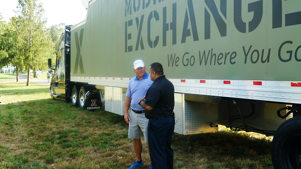 Retired LTG Raymond V. Mason, director of Army Emergency Relief, left, talks with the Exchange's VSO/MSO Outreach Manager Jose Hernandez in front of a mobile field Exchange at A Military Tribute at the Greenbrier, the first stop of the 2019-2020 PGA Tour.