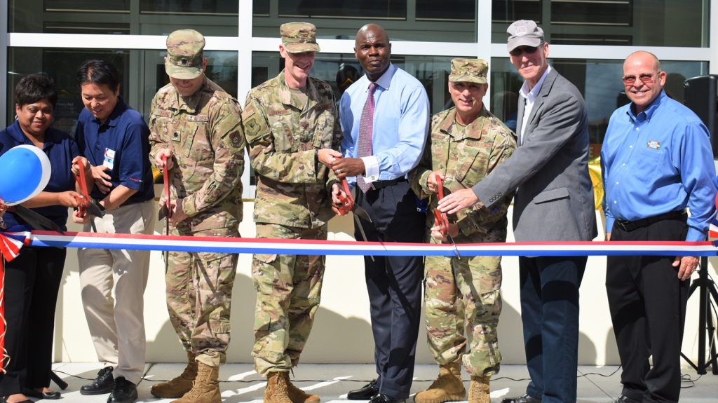 Pacific Region Commander Col. Scott Maskery and Exchange General Manager Antonio Porter, both center, help cut the ribbon on Kadena AB's new Express.