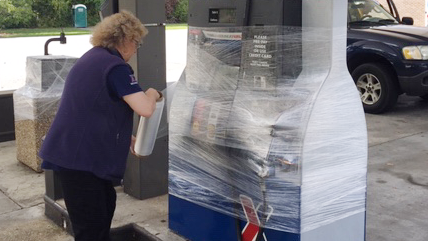 Shift Manager Marion Koenig wraps a gas pump in protective plastic at the Express before the store closes.