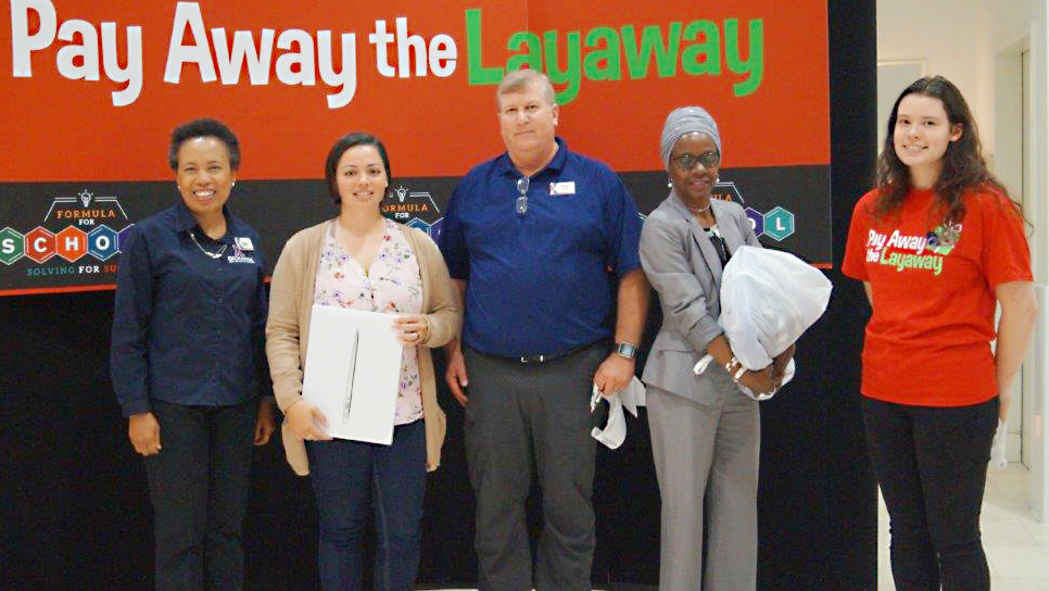 Left to right, Main Store Manager shopper Elaine Thomson, Operations Manager David Parker; shopper Bonita Jones, and Customer Service Associate Kayley-Ann Hanner celebrate the Exchange paying off the layaways. Thompson's MacBook and Jones' backpack and kids' clothing were paid off.