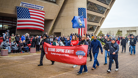With the wind a little calmer, Exchange managers and associates pass in front of the Dallas City Hall. The 2019 Veterans Day Parade was held to commemorate the 75th anniversary of the Normandy invasion.