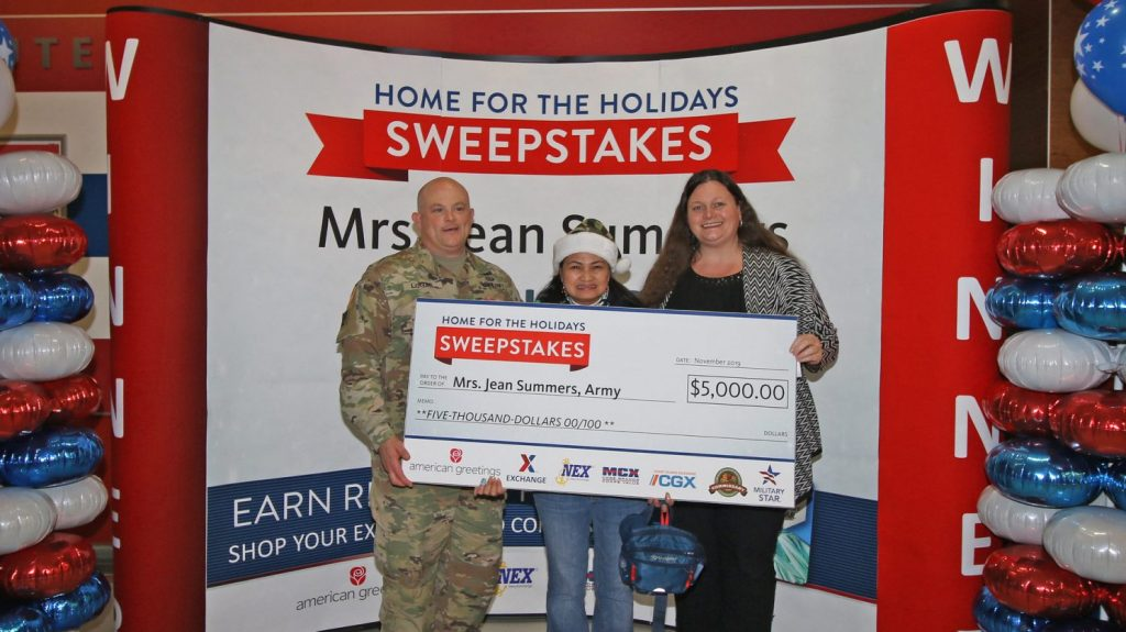 Fort Stewart Garrison Commander Col. Bryan Logan and Exchange General Manager Hollie Heft Morales, right, present Army sweepstakes winner Jean Summers with her prize. Photo by SSG Todd Pouliot