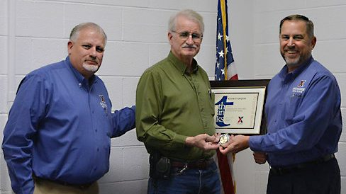 From left, Facility Manager Ray Estes, 50-year associate Kevin Gaquin and Real Estate Directorate Senior Vice President Mike Smietana mark Gaquin's achievement.