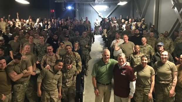 "Director/CEO Tom Shull, in red shirt, and Ken Caldwell of The Walt Disney Studios join troops in Afghanistan for the showing of the new ""Star Wars"" movie."
