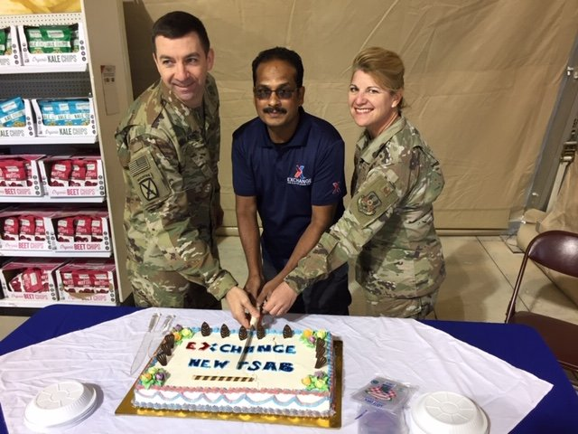 COL Scott McFarland, commander of the Exchange's Europe/Southwest Asia Region, helps cut the cake during grand-opening ceremonies. He is joined by Store Manager Salam Abdus and  EMSG Commander Col Julie Boit.