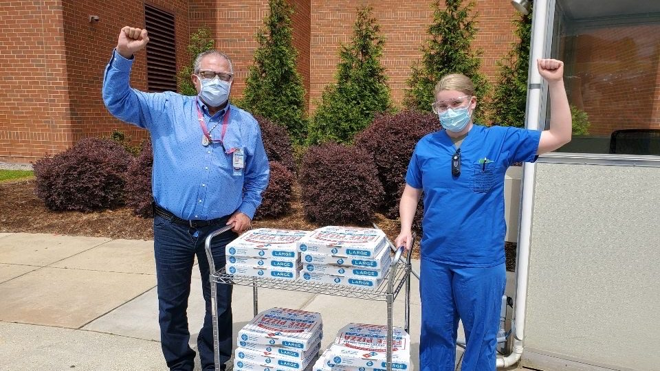 Domino's Elisa Hicks delivers pizza to a staff member of Fort Bragg's Womack Army Hospital.