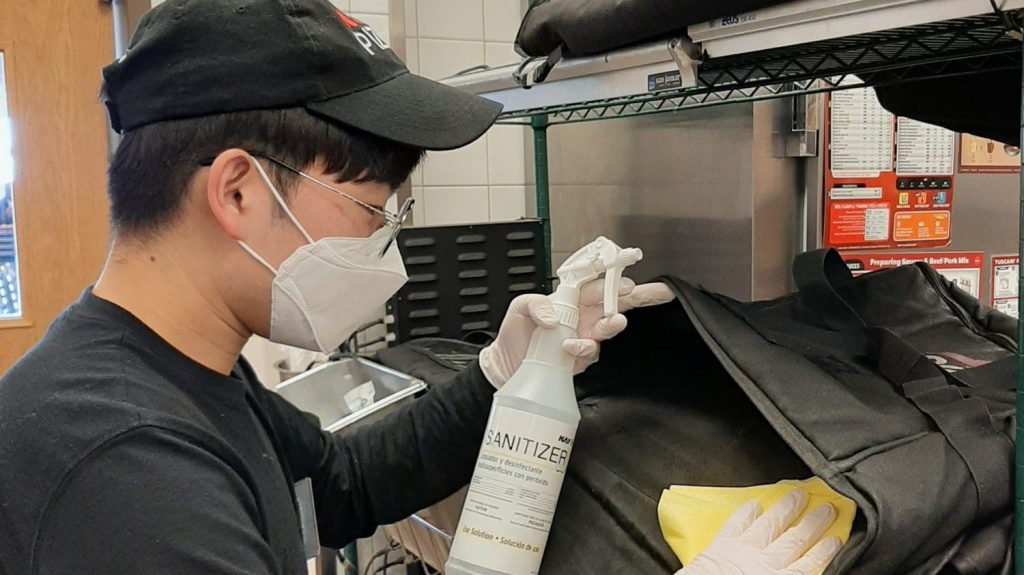 Camp Humphreys Exchange food service worker Han Sang-uk sanitizes a Pizza Hut delivery pouch.