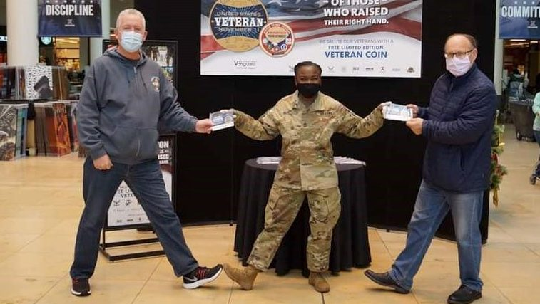 Sgt. Maj. Julia Henry (center), senior enlisted advisor of the Exchange's Europe/SW Asia Region, hands out challenge coins to Air Force Veterans Master Sgt. (retired) Richard Rhodes (left), and Senior Master Sgt. George Labbay (right) in honor of Veterans Day at the Kaiserslautern Military Community Center Exchange in Germany Nov. 11. (courtesy photo)